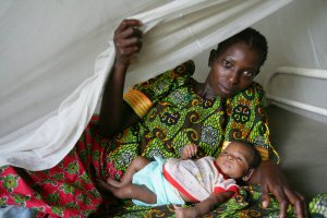 A woman reclines in bed with her newborn under a UNICEF-provided mosquito bednet.