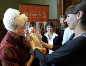 Parliamentary assistant to the Minister of Health and Long-Term Care, Liz Sandals (left), takes one-month-old Eloise Akiyama from mother Jenna Robertson (right) as Katrina Kilroy, Midwife and President of the Association (centre left), and NDP Health Critic France Gelinas look on, following a luncheon for the Association of Ontario Midwives' Birth Centres in Ontario campaign at Queen's Park in Toronto, Thursday, May 5, 2011.  MARKETWIRE PHOTO/Association of Ontario Midwives