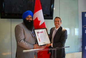 Minister of State for Democratic Reform Tim Uppal presents a framed copy of Bill C-442, the Act to establish a National Holocaust Monument to Avi Benlolo, President and CEO of Friends of Simon Wiesenthal Center for Holocaust Studies.