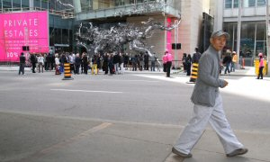 One of China's most influential living artists, Zhang Huan, walks past his permanent public sculpture, Rising, following its unveiling at Living Shangri-La in Toronto, Saturday, May 5, 2012. The large-scale exterior sculpture, which measures 21.98 x 19.8 x 4.8 metres, will permanently reside at the University Avenue entrance to Shangri-La Hotel, Toronto. The Canadian Press Images PHOTO/Living Shangri-La, Toronto
