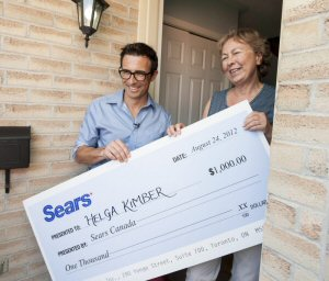 Sears CEO Calvin McDonald delivers the Wish Book grand prize to Helga Kimber of London, Friday, August 24, 2012.  The Canadian Press Images PHOTO/Sears Canada