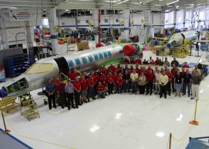 Des membres de l'équipe de Wichita se tiennent fièrement à cote du premier biréacteur Learjet 75 de série.