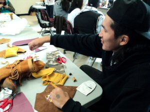 Webequie students work into the night creating their moccasins
