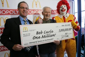 """Les Hodgins (left) of McDonald's Canada and Ronald McDonald present Bob Curle (centre) with a cheque for his $1 million Monopoly(R) prize, Thursday, November 29, 2012, in Selkirk, Manitoba. Curle, 71, won the grand prize after finding both the """"Park Place"""" and """"Boardwalk"""" game stamps on his regular large coffee, the odds of which were 1 in 307 million. The Canadian Press Images PHOTO/McDonald's Restaurants of Canada Limited"""