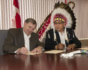 Brendan Dolan, President, ATCO Pipelines (left) signs agreement with Chief Marvin Yellowbird of Samson Cree Nation.