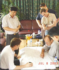 Robert Friedland (sitting on left) and Chen Jinghe (standing on left) review a mineral prospects map in 2003.