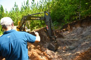Alabama Graphite's excavator easily cuts through the Coosa Graphite Project's soft-rock, graphite-bearing material during the Company's summer 2015 diamond drill program (July 9, 2015).  Source: Alabama Graphite Corp.