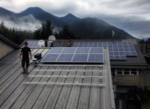 A representative from Hakai Energy Solutions completes a final check of the Kitasoo/Xai'Xais community solar installation on the roof of the Kitasoo Community School, earlier this month, in Klemtu, British Columbia. The project is a result of the support of Bullfrog Power and major contributions by a coalition of partners.