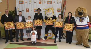 De gauche à droite, Pat Finelli (chef de la direction du marketing de Pizza Pizza), Paulo Carvalho (gestion des commandites de Pizza Pizza), la patiente Rhys Jones (9 ans), Jennifer Laughton (vice-présidente de la Fondation du McMaster Children's Hospital), Stripes, la mascotte des Tiger Cats de Hamilton, Angie Ramalho (Children's Miracle Network), Tommy Turner (directeur des partenariats commerciaux, Children's Miracle Network), Bruiser, mascotte des Bulldogs de Hamilton et, à l'avant, la patiente Heba Mohamed (3 ans) célèbrent à Hamilton, le jeudi 28 janvier 2016, les deux campagnes de 2015 de Donnez avec le sourire qui ont amassé une somme record de 400 000 $ à l'intention du Children's Miracle Network.