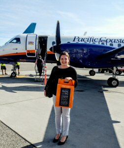 Pacific Coastal Airlines' passenger Gaelle Madevon from Victoria shows off her complimentary wine carry box upon arrival at Kelowna International Airport (YLW). The box full of wine will fly for free under the airline's fifty pounds of free checked baggage policy.