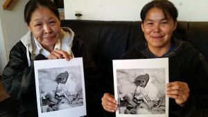 In September 2014, Ashevak Geetah (left) and her daughter, Eva Geetah (right) reconnected with their father and grandfather, Eetooloopak, after seeing his photo, which was taken in Iqaluit, Nunavut in March 1956. Black-and-white photo by Gar Lunney (LAC / PA-180267).