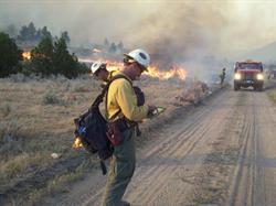 Fire-fighting hotshot crew member checks his map on his iPad
