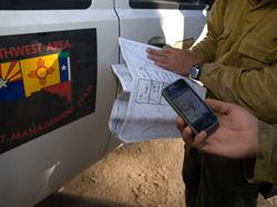 A digital map on a mobile device is held up next to a large paper map