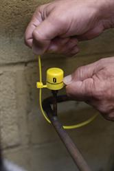 Applying tamper-evident straps to an AC&R service port to prevent refrigerant cross-contamination
