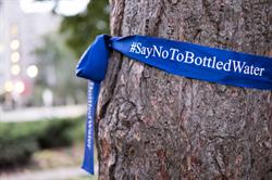 Blue ribbons marked with #SayNoToBottledWater wrapped trees at Queens Park today