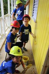 A Canadian donor and her kids help paint the walls of the new Lloyd's Basic School.