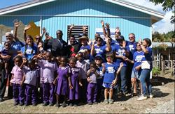 Volunteers and students of Lloyd's Basic School celebrate the opening of the new school with Jamaica's Minister of Education, Ruel Reid.