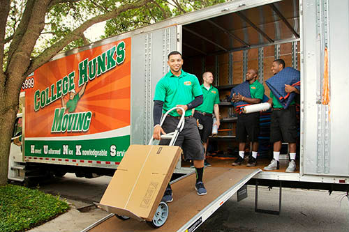 A team of movers in a College Hunks moving van