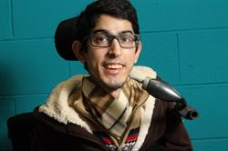 A young man in a wheelchair happy to have access to his mobile device through the LipSync