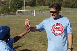 "A Challenge volunteer provides an athlete a ""high five"" in 2014"