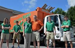 Six people standing in front of a College HUNKs truck with orange trailer.