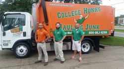Three members of Rockford, IL College Hunks Hauling Junk stand by their junk hauling franchise truck