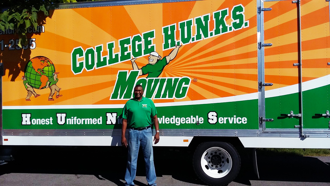 Michael Smith proudly poses in front of his new College Hunks moving truck