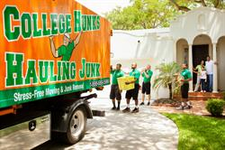 A uniformed team of College H.U.N.K.S. Hauling Junk crew members load furniture and boxes into the