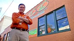 Man with orange shirt poses in front of his College Hunks storefront