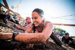 Tough Mudder participants crawl through muddy obstacle.