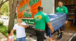 College Hunks movers loading furniture into their truck while a father and daughter look on
