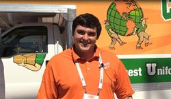 Man in orange shirt standing in front of moving truck.