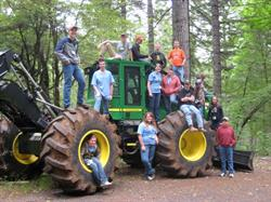Students at 4-H Leadership Camp in Oregon gather around a heavy earth mover for a photo.