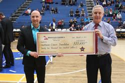 Sterling Nielsen of Mountain America (c.) and Steve Starks, president of the Utah Jazz (r.) present a $42,000 check to Paul Huntsman, who represented the Huntsman family at the San Antonio Spurs game on April 12, 2017.