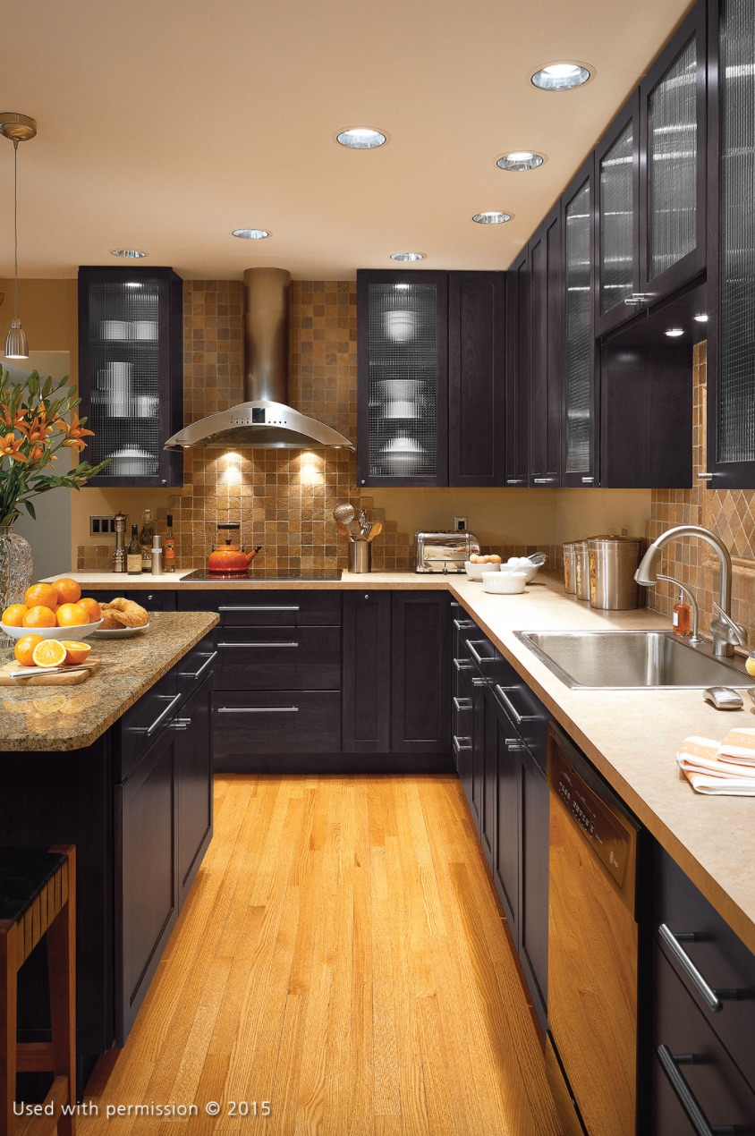 A modern kitchen remodel, with black cabinets, light-brown hardwood floors and stainless steel fixt