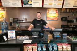 An Erbert and Gerbert's franchisee stands smiling behind the register at one of his locations.