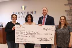 Branch Manager Michael Brine presents a $1,000 donation to local charity Carol Matheys Center for Children and Families.