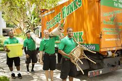 Four men hauling junk into the back of a CHHJ Junk truck.