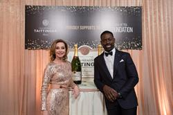 Sharon Lawrence and Sterling K. Brown sign a Methuselah bottle of Champagne Taittinger to raise money for the SAG Foundation's critical Emergency Assistance program during the 24th Annual SAG Awards.